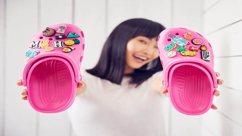 Image of an Asian woman holding a pink pair of bedazzled Crocs shoes.